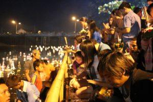 祈りを込め、灯篭を流すタイの人々