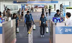 感染症対策をする空港の職員たち